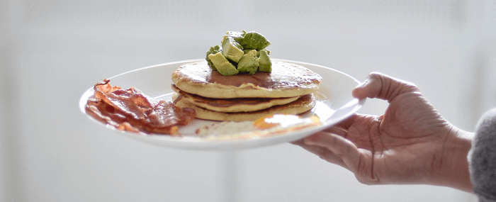A plate of keto pancakes with avocado on top