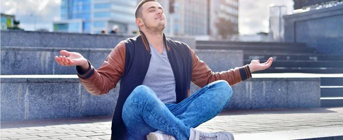 Man sitting in public practicing transcendental meditation