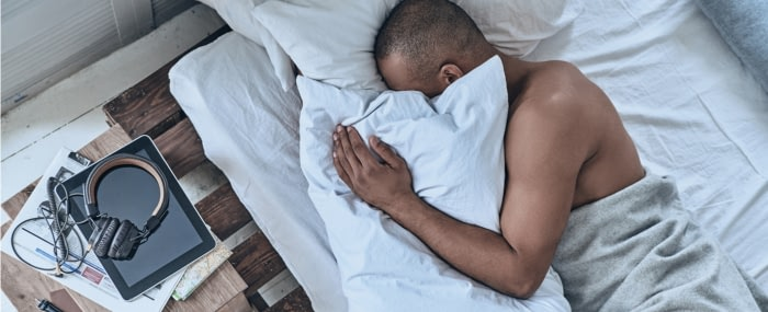Man sleeping on his side using a body pillow
