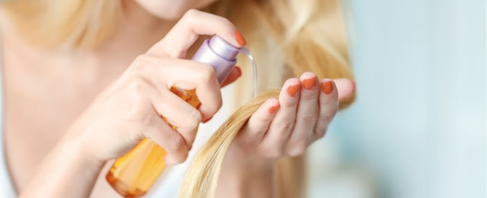 woman applying an external hair-care product to her hair