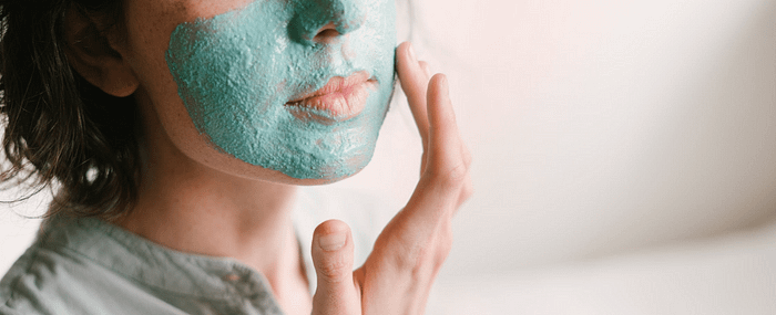A woman applies a skincare mask as part of her self-care routine