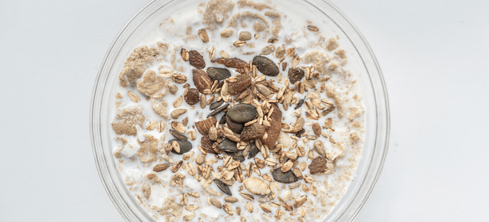 A bowl of oats and milk that help improve gut health reducing bile acids & lowering cholesterol