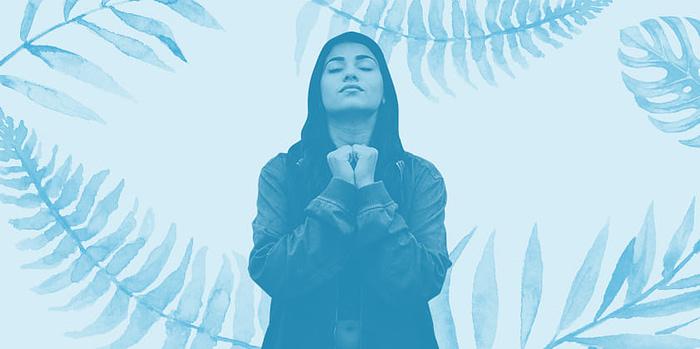 female meditating among blue leaves background