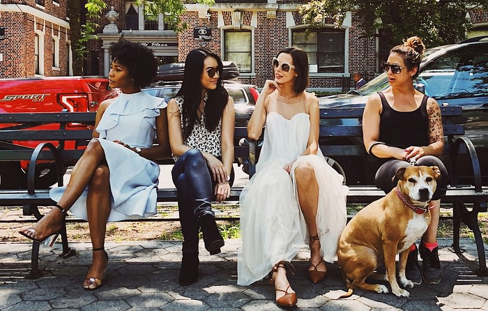 group of four females with one dog chatting about self care staycation