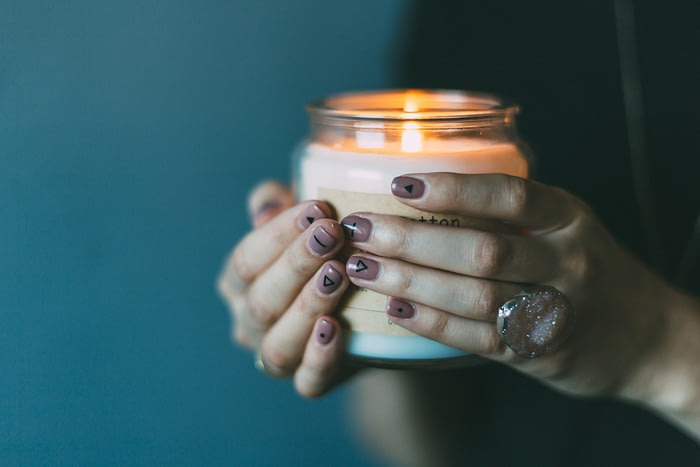 a CBD infused candle being held be a woman