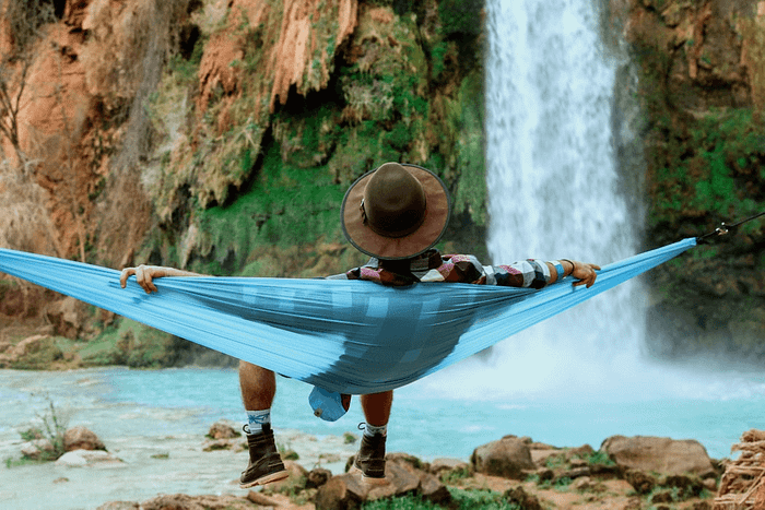 woman sitting on hammock in front of waterfall relaxing to the calming effects of water