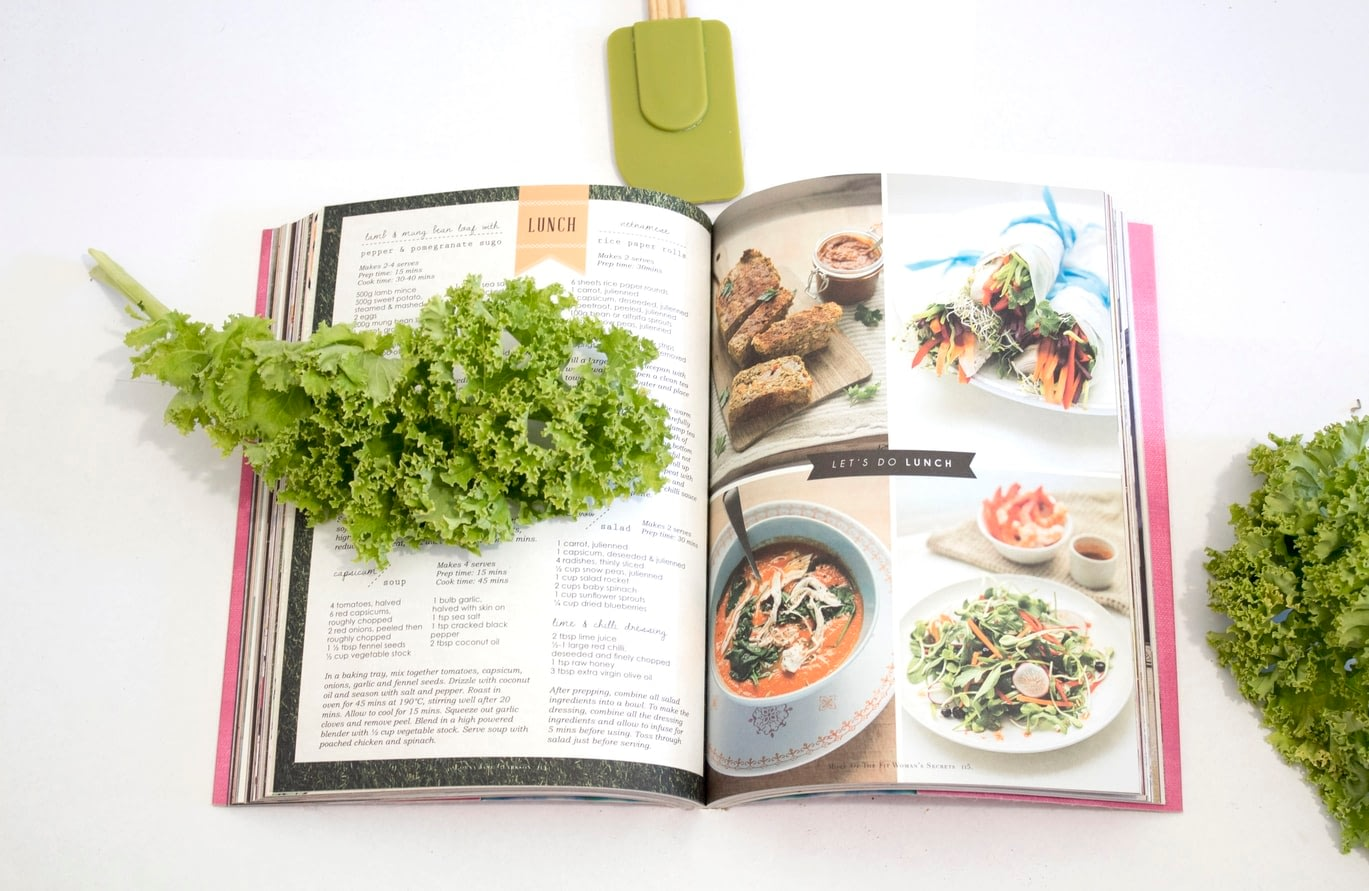 healthy recipe book open with kale resting on the cover