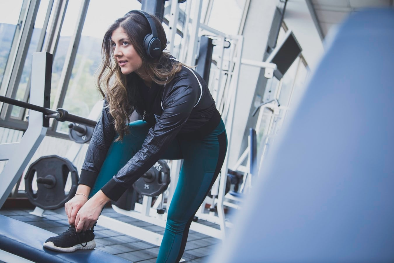 woman looking in mirror while listening to a playlist of songs to workout to