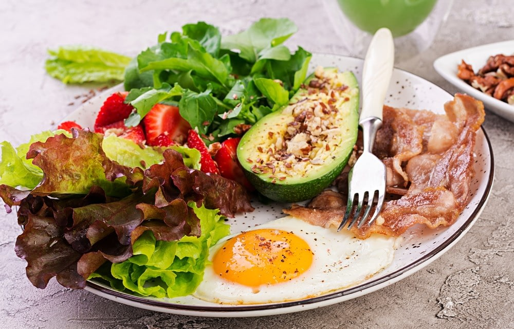 eggs with avocado and salad with strawberries on a plate as part of keto diet recipes