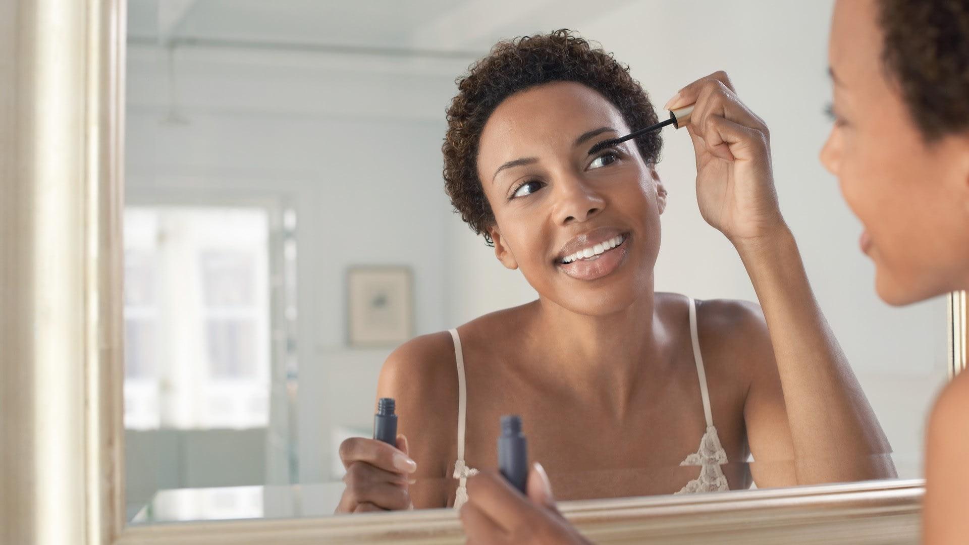 woman applying mascara in mirror using makeup tips