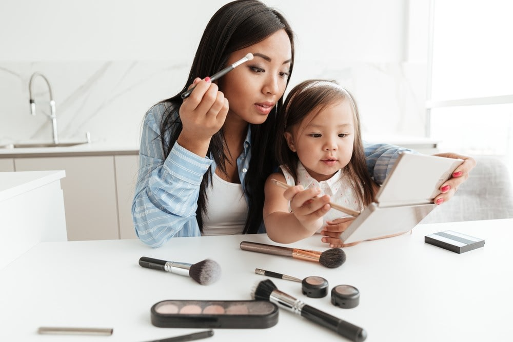 Mother introducing child to makeup by applying eyeshadow