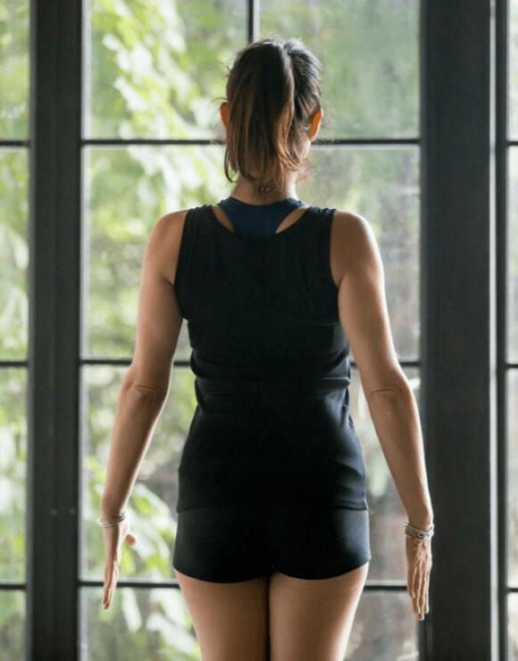 Woman facing windows practicing the Mountain yoga pose