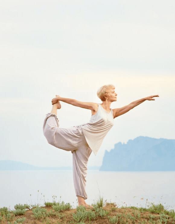 Older woman practicing the natarajasana yoga pose a top a hill