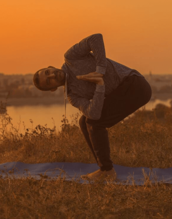 Man in a field practicing the Prayer Twist Yoga Pose