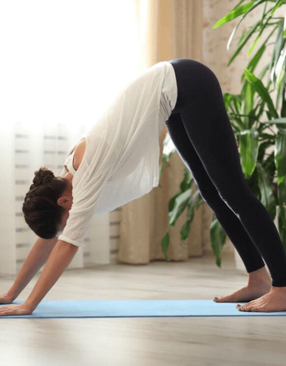 Woman practicing the downward facing dog yoga pose
