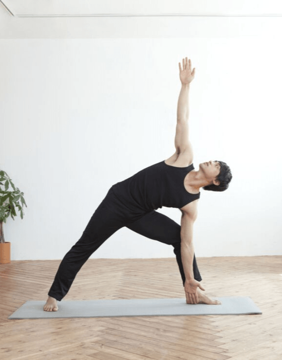 man practicing the Trikonasana yoga pose