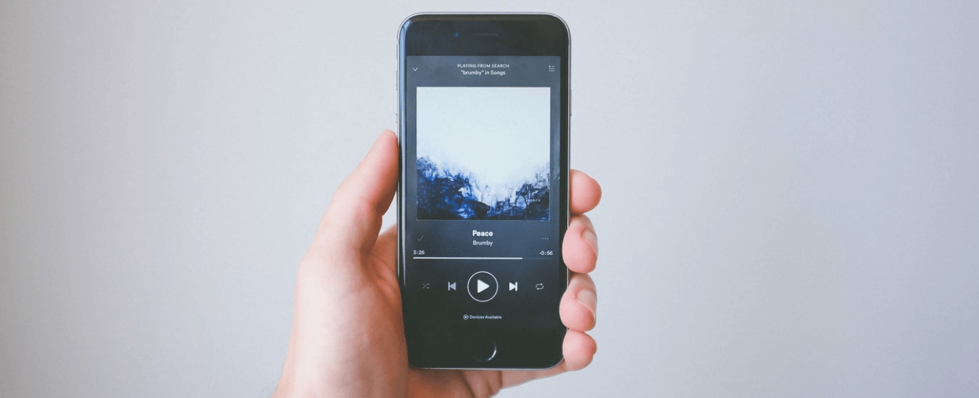 hand holding phone up scrolling through best music for yoga