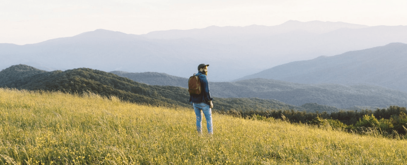 Man standing in field looking into the distance thinking about living a happy life