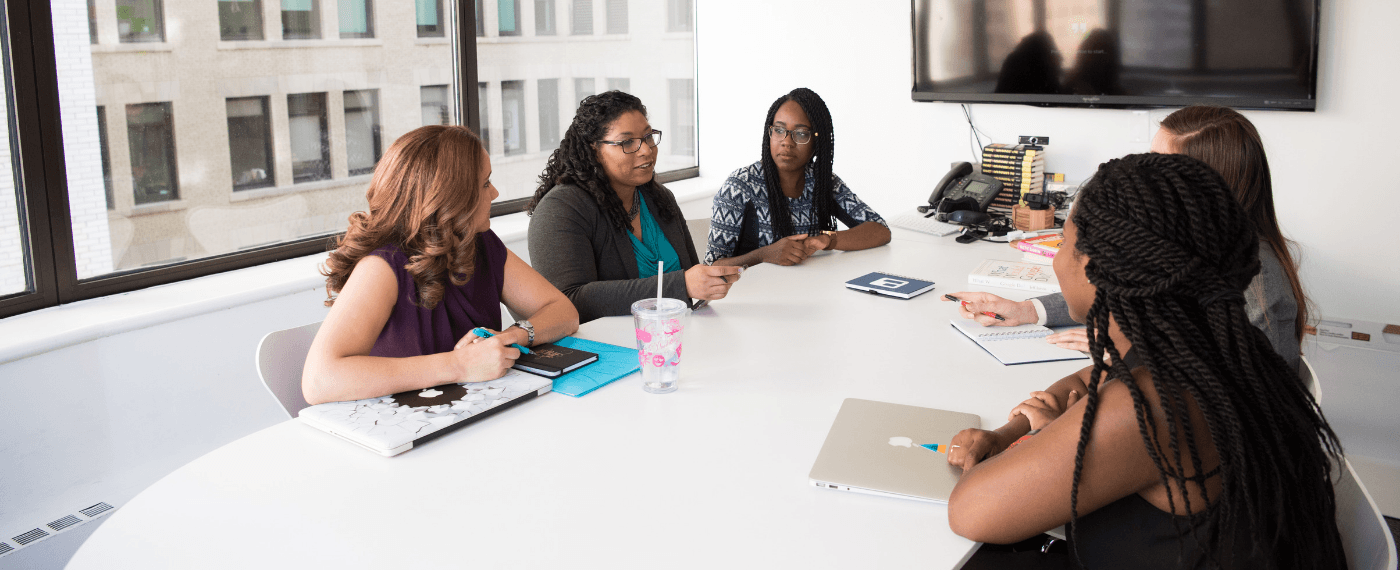 group of business women discussing the importance of employee motivation in an office