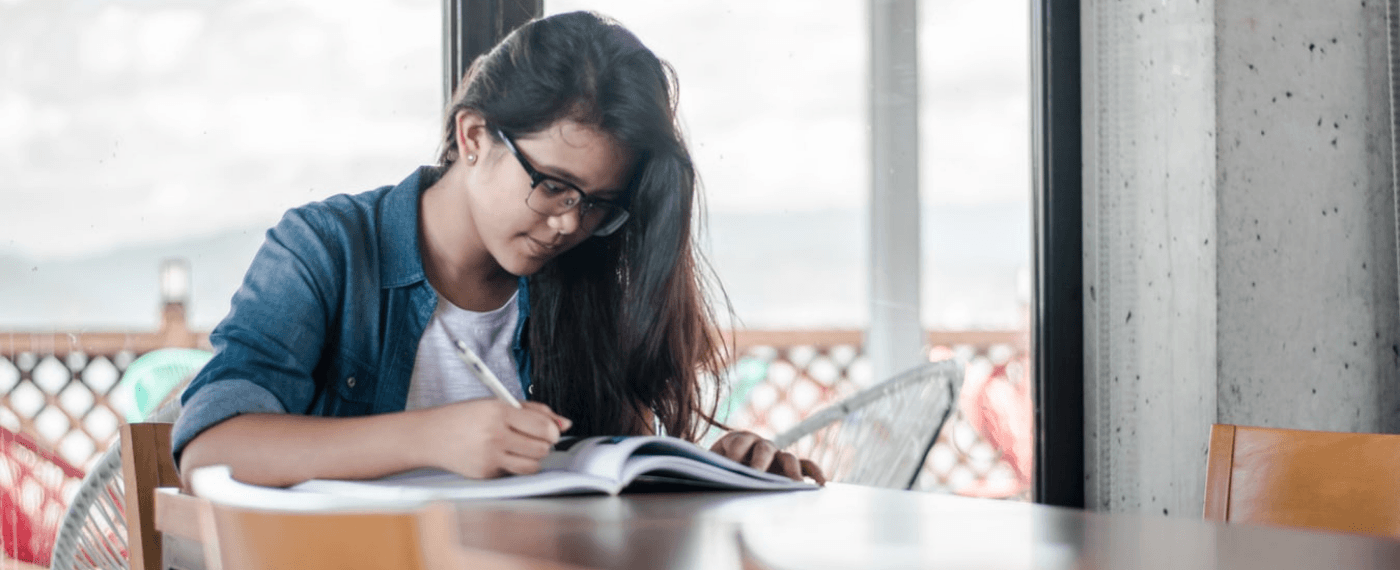 girl sitting at tbale writing in journal about improving yourself