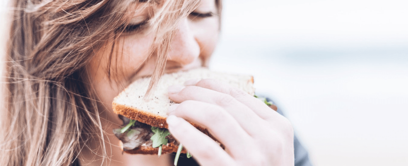 A woman enjoys biting into a sandwich