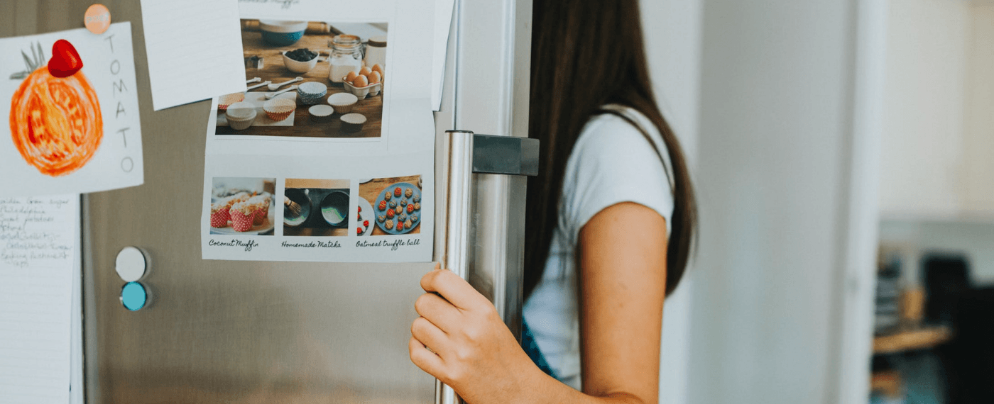 A girl looks into the fridge, looking for her serotonin fix