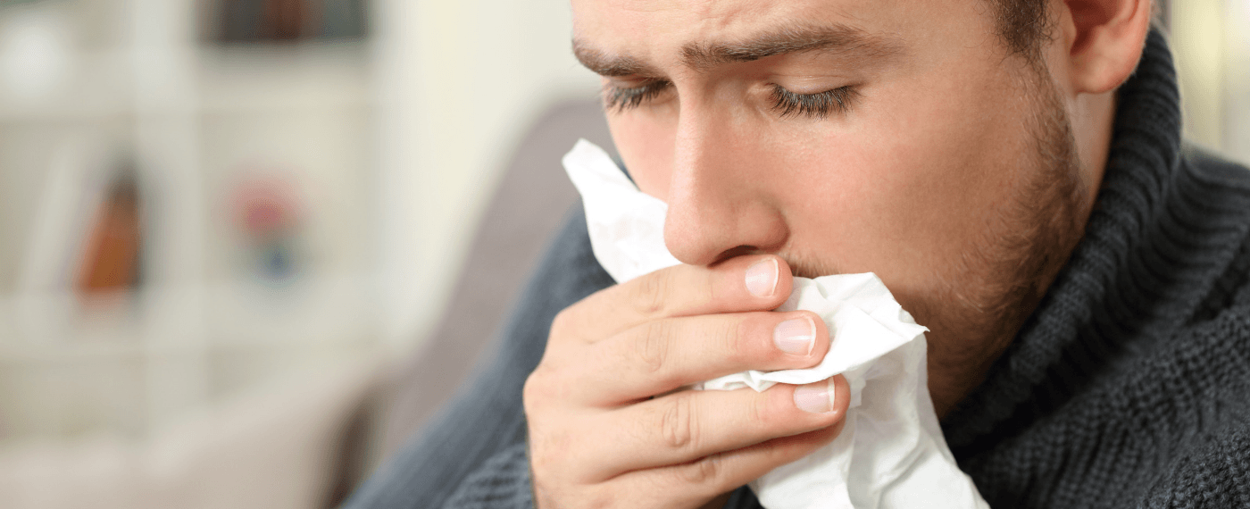 Man holding tissue to mouth to cover cough