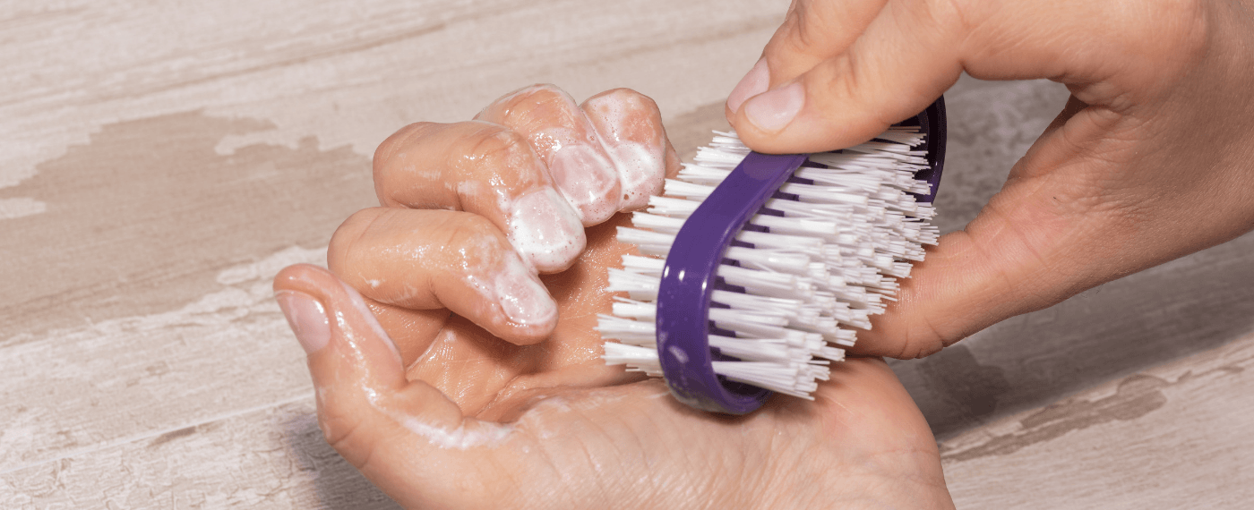 Woman scrubbing nails with a bristle brush