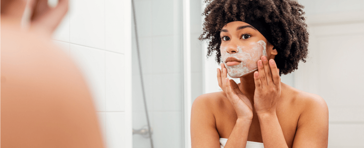 a young woman practicing self care through a skincare routine