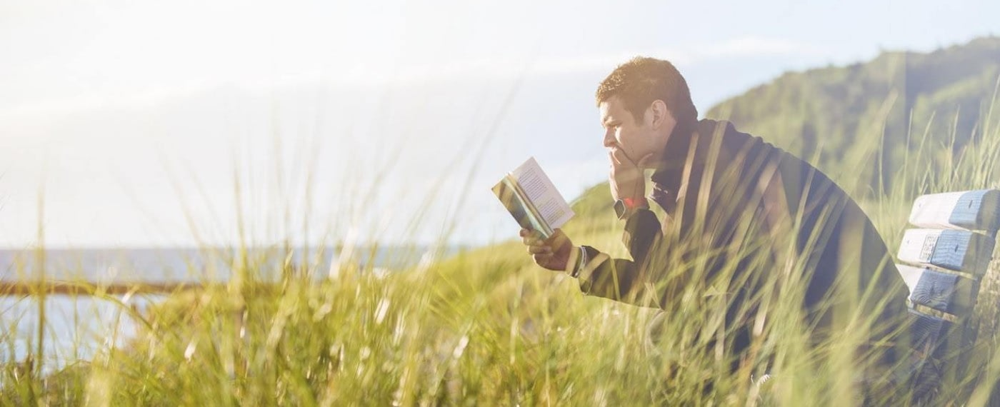 man reading a book in a field about making time for intimacy