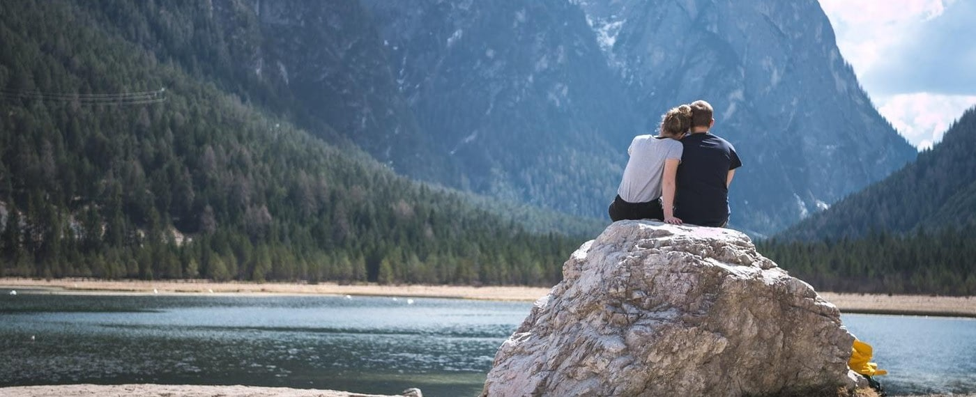 A couple sits enjoying an intimate moment on a rock by a lake