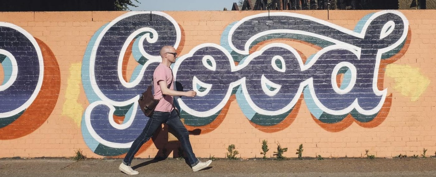 A bald man walks purposefully along a wall with graffiti