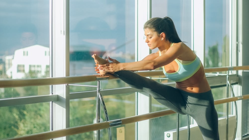 Young girl stretching her leg out over a balance beam