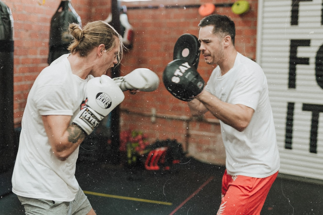 male boxing trainer helping male boxer practice