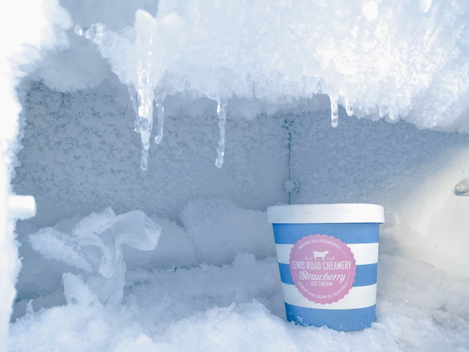 The frozen ice inside a freezer with a quart of strawberry ice cream