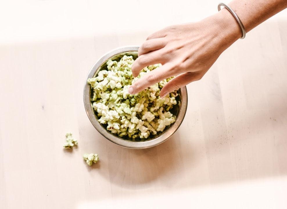 A hand reaching for a bowl cbd popcorn