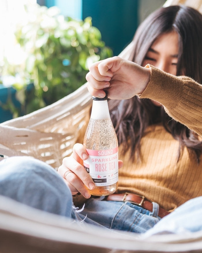Young girl twisting the cap off a rose pink cbd sparkling water