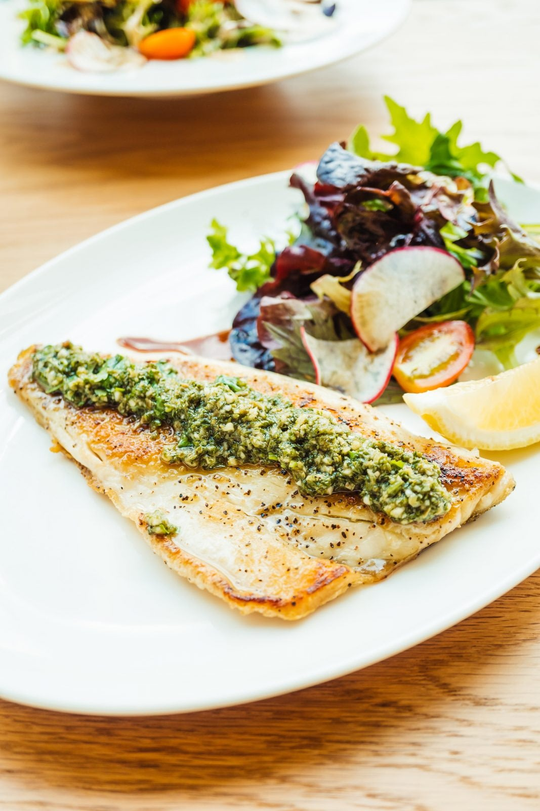 Grilled fish with pesto sauce with a side of vegetables