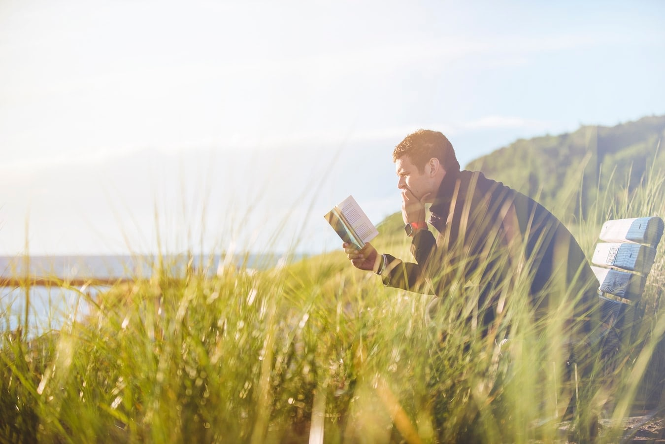 Healthy man reading a book while sitting on a bench in a field