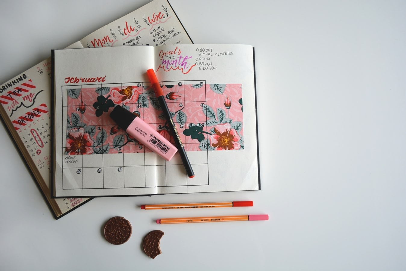 A goal calender open on top of a daily planner with a highlighter and pencils