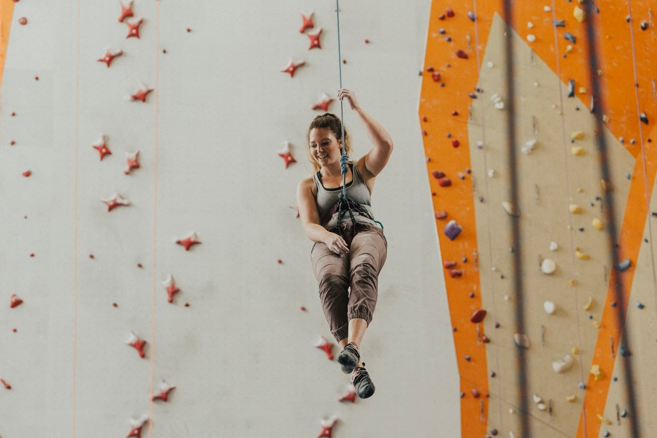 woman rappelling down a rope during indoor rock climbing