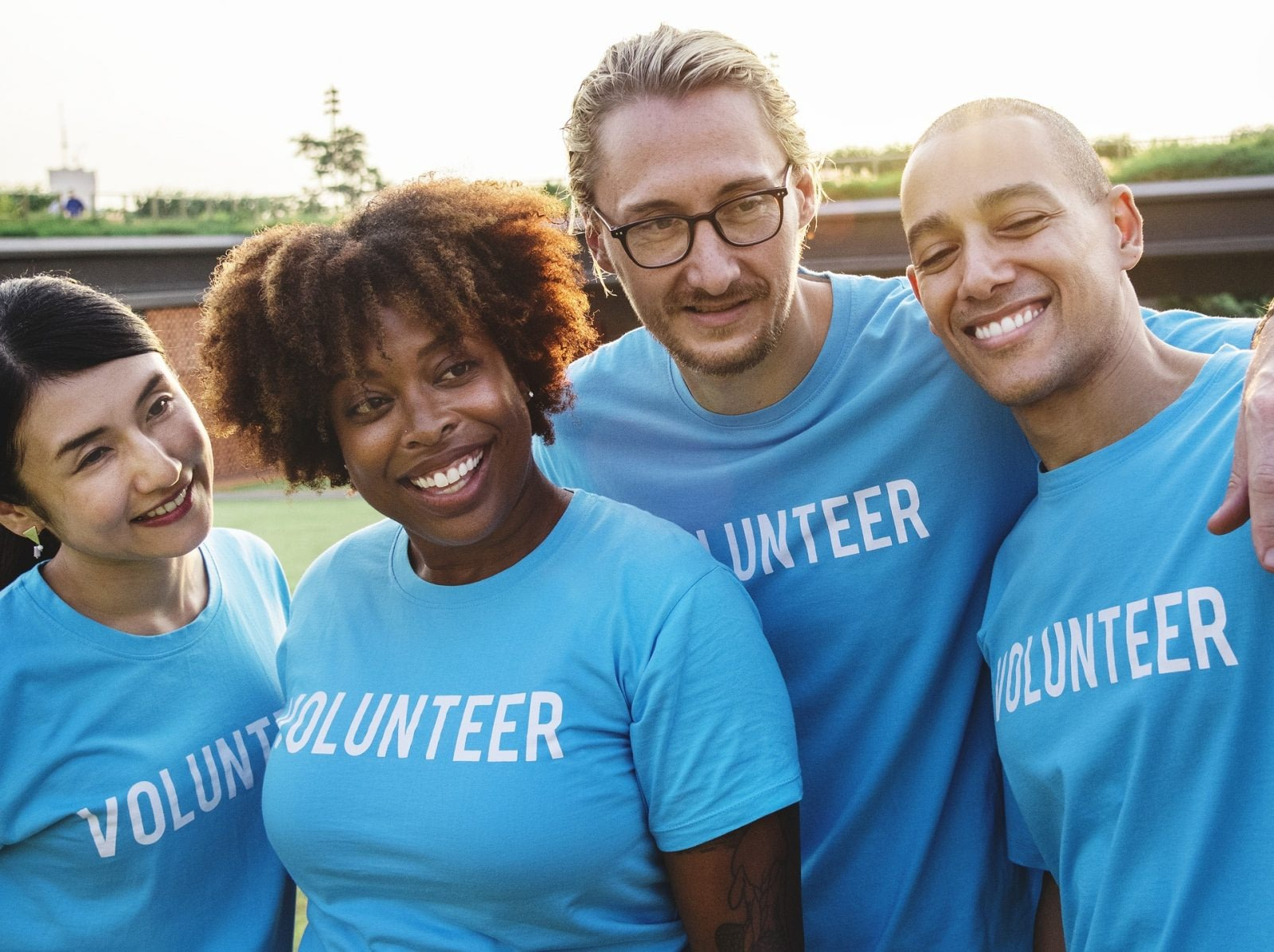 Two men and two women wearing volunteer's t shirts smiling