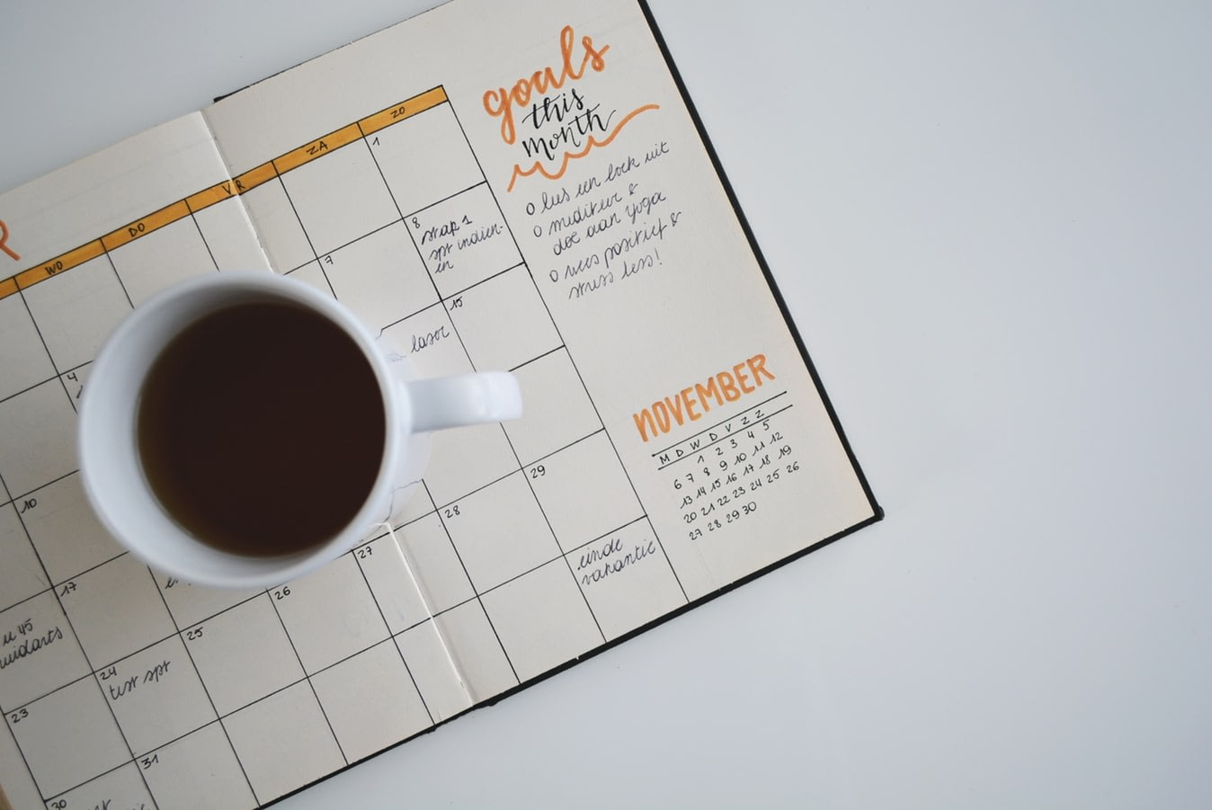 Cup of coffee sitting on top of an empty monthly goal planner