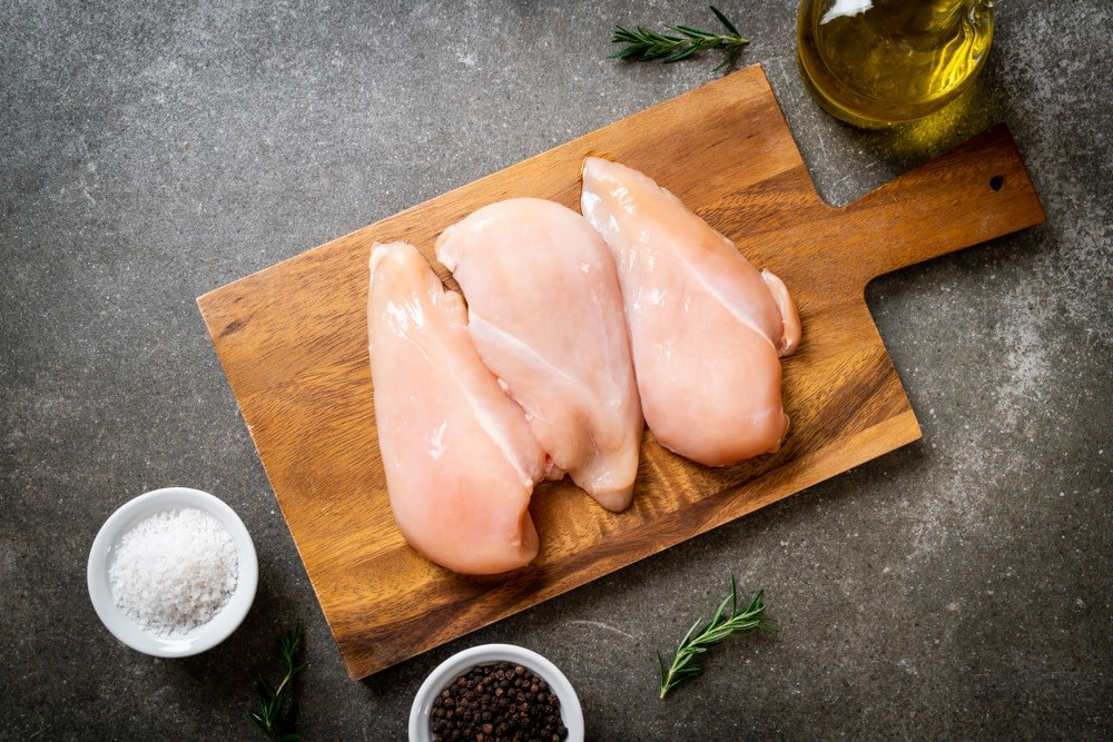 Raw chicken breasts in top of a wood plank with salt, pepper, and oil on the side