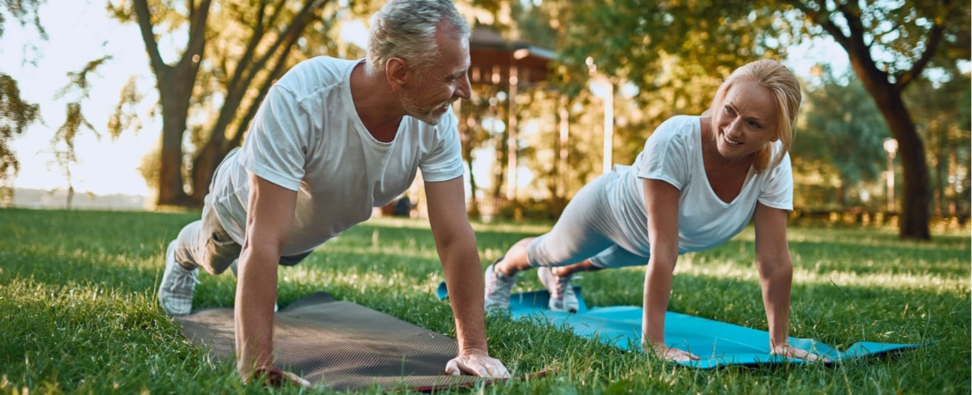 man and woman on yoga mats in the woods practicing joint strengthening exercises