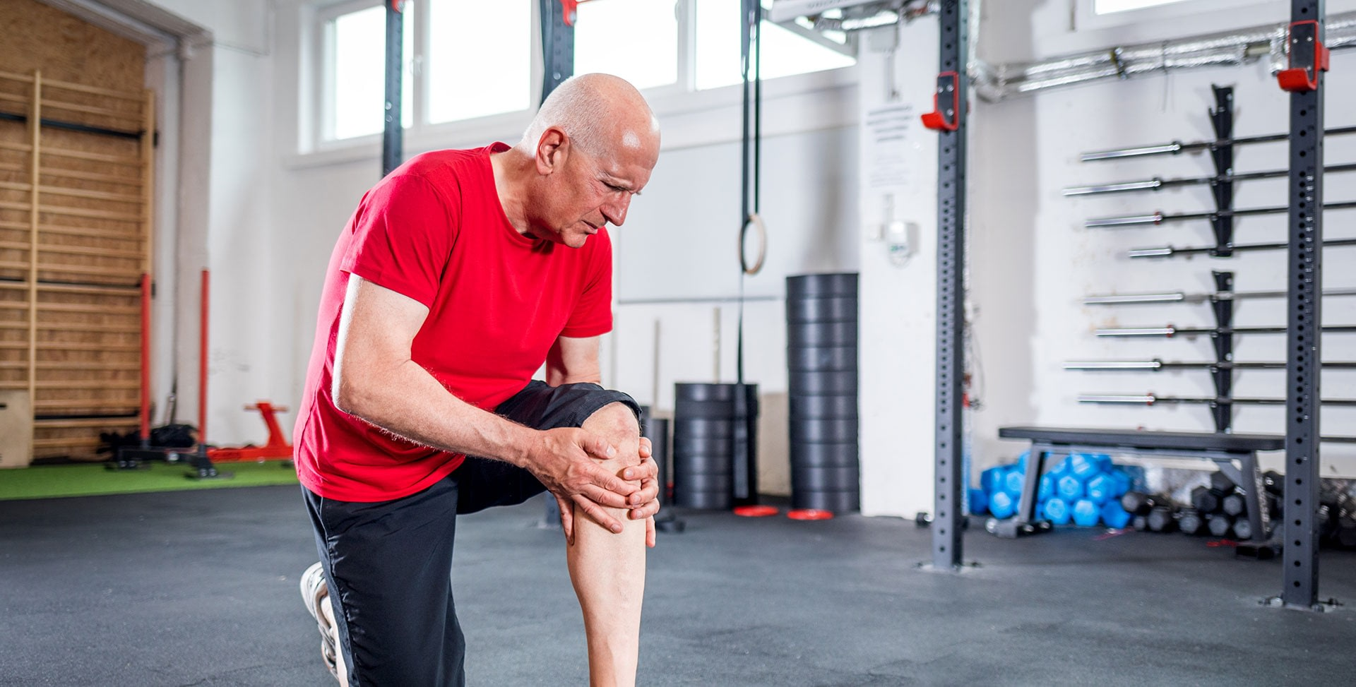 older man with knee pain in gym trying to keep joints healthy