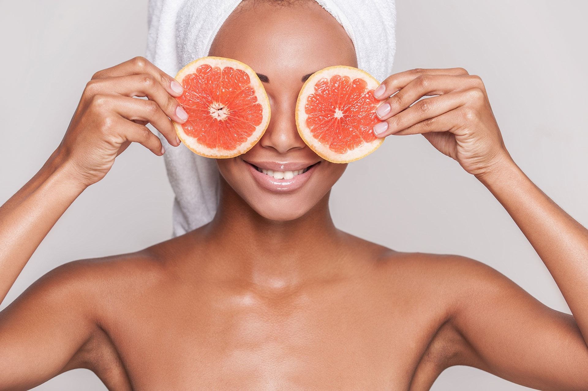 Woman holding grapefruit slices in front of her eyes