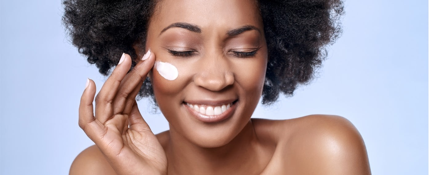 woman smiling while applying lotion to her face for skin care routine