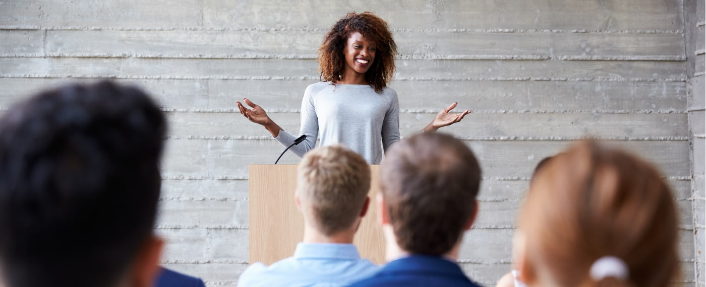 Female motivational speaker smiling in front of a group of listeners