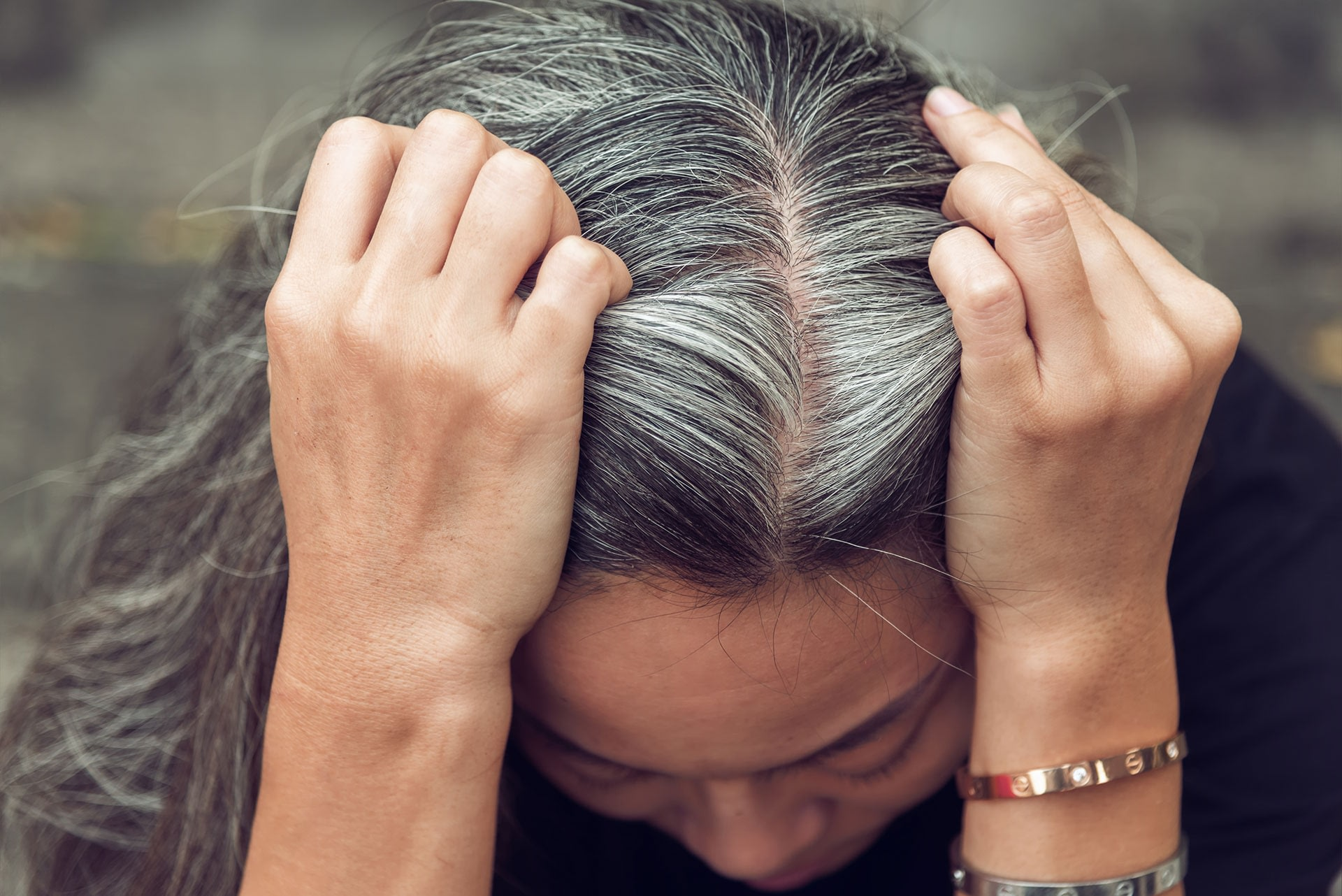 lady parting hair to show gray hair